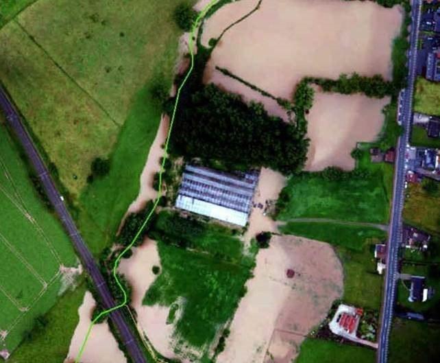 Een landbouwbedrijf moet heel wat water slikken, afwaarts van de spoorweg in Herne.