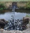 De drempels van de vistrap zijn opgebouwd uit een houten damwand en omringd door ruwe breuksteen.