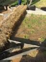 Dam van strobalen van ongeveer 50 cm hoog en 20 tot 30 cm ingegraven, eventueel verankerd met een dubbele rij houten palen.