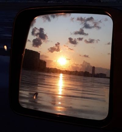Achteruitkijkspiegel jeep bij zonsopgang op het strand