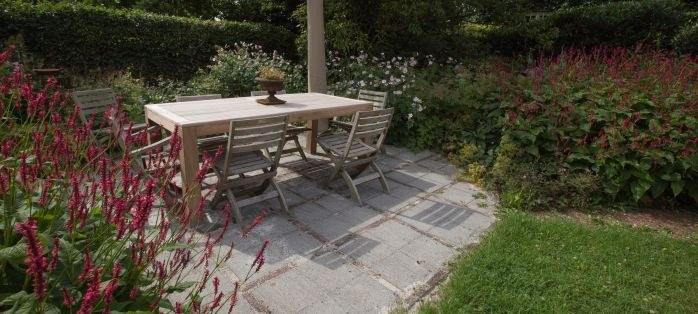 Foto terras met brede voegen, zodat water kan infiltreren. Het water dat afstroomt infiltreert in de tuin.
